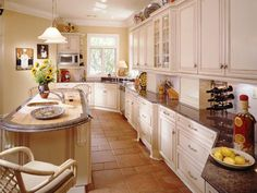 Glazed French-country cabinetry graces this large gourmet kitchen. The butcher-block-and-granite island is an eye-catching element that melds form with function. The stone flooring adds a dynamic dimension to the space. Design by Jackie Glisson.