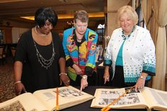 "Marilyn Sands, left, Maria Siemon and Allyson Samiljan view old newspaper articles featuring the YWCA at its annual ""Recognition Luncheon,"" which took place at Bear Lakes Country Club located in West Palm Beach. ."