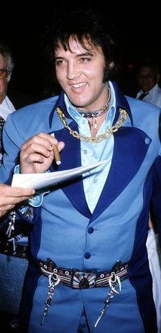 Elvis in blue while smoking a cigar at JFK airport on July 19, 1975 Saiba mais sobre Lendas da Músicas no E-Book Gratuito – 25 VOZES QUE MUDARAM A HISTÓRIA DA MÚSICA em http://mundodemusicas.com/vozes-musica/