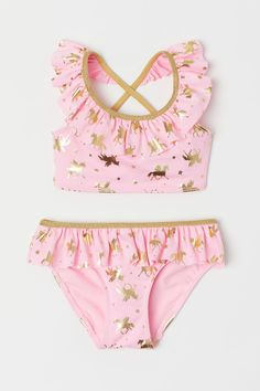 Bikini with a shimmering gold-colored pattern. Bikini top with glittery gold-colored elasticized shoulder straps crossed at back. Ruffle at top. Lined front. Fully lined bikini briefs with ruffle at top. Baby Bikini, Bikini Rose, Rosa Bikini, Baby Girl Swimsuit, Pink Bikini, Sleepwear Women, Pajamas Women, Kids Fashion, Womens Fashion