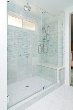 Large walk-in shower big enough for two, with a full bench seat and two shower heads. Relaxing sea green and white color scheme.