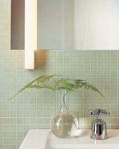 Fern fronds in a clear-glass vase on the edge of the sink continue the room's natural theme.