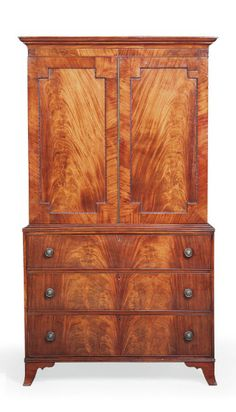 AN EARLY VICTORIAN MAHOGANY LINEN PRESS   CIRCA 1840   The panelled doors with gadrooned border enclosing three slides, the lower section with three long drawers with brass handles, on slightly splayed legs  87¼ in. (222 cm.) high; 48½ in. (123 cm.) wide; 19¼ in. (49 cm.) deep