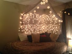 Icicle lights + tulle + paper lanterns and about 100 thumb tacks. Voila! Warm and fun :)   I used to have this in my room!
