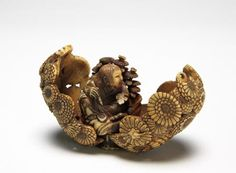 A barrel-shaped container made of chyrsanthemum and hinged at the bottom Inside is the figure of Kikujido, a sennin (immortal being) who wrote the magic characters of longevity on chrysanthemum leaves
