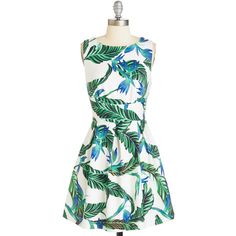 Youre sure to have everyone completely smitten when you enter the room in this printed white dress! Ferns and leaves in shades of green and blue decorate the s…