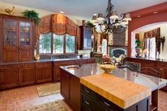 An English country kitchen with heavy patterned and tasseled drapery and floral area rugs. The gray granite kitchen island has a butcher's block built onto one of the corners. A ceramic bowl sits as decoration on the center of the island.