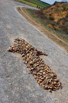 Por todo el camino los peregrinos siguen no solo los letreros marcados por las flechas amarillas y las vieiras, sino también flechas construidas de piedra que marcan el camino hasta Santiago de Compostela.