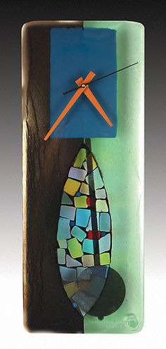 Art Glass Clock by Nina Cambron   Artful Home. Black & green iridescent glass form the perfect portal in this fused glass clock. Teal and a myriad of translucent shards and chunks of color accentuate the side to side sweeping motion of the pendulum behind.