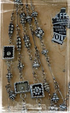 Necklaces with frame connectors that have rhinestones and watch parts in them, along with rhinestone beads and spacers.