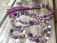 Approximately 6.5 mm beads gemstone bead mala small enough for wearable length 108 multi-color tourmaline Faceted ruby guru bead Hand knotted on dark burgundy string Cotton Tassel Tourmaline gemstone is a semi-precious mineral stone well known for its incredible ability to aid in the