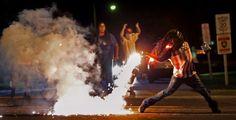 En la imagen, un manifestante lanza una bengala a la policía durante una protesta en Ferguson, Missouri (EE UU), el 13 de agosto de 2014.