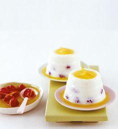 Italienisches Milch-Dessert mit Himbeer-Orangensauce und Vanille.
