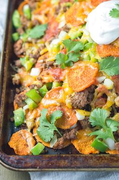 Healthy nachos layered with homemade sweet potato chips, seasoned ground beef, fresh onions and peppers, shredded cheddar cheese, sour cream, and salsa.
