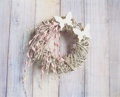 Piękny wianek wykonany na oryginalnym białym podkładzie, ozdobiony jasno różowymi gałązkami z maleńkimi baziami , całość uzupełniają drewniane motyle. Wianek może ozdabiać stół, ścianę lub drzwi....