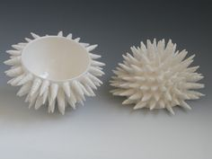 """CLOUDNINE. 4 x 7 x 7"""". Katherine Dube 2000-2012.     CloudNine vesselis a multi-award winning original design created from porcelain clay. The vessel body is wheel-thrown. Each spiral is hand-rolled from thinribbons of porcelain; then cut, altered, and individually attached. The vesselis glazed a glossy white."""