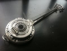 Heavy Metal Banjo by ShaneMartinDesigns.deviantart.com on @deviantART  3 foot banjo made from scrap metal The body is made from an old car fly wheel and clutch cover, the neck is a piece of rebar and part of a steel erectors spanner ,the head is made from an old pair of pliers some valves from a car engine and a piece of chain gear from a push bike, oh and an old iron cross belt buckle The strings are from a bass guitar
