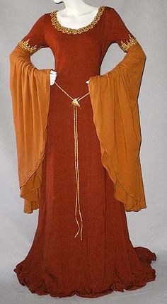 Nice medieval-style gown in warm brownish/orange autumn shades with gold trimmings and gold trim as medieval belt plus ivy leaf brooch.