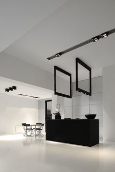 All-white interior with dark accents and Kreon lighting. Designer unknown.