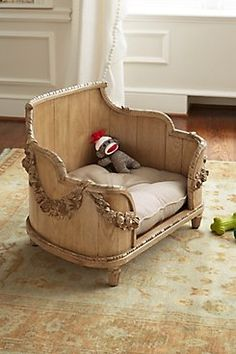 """Floral Swag Dog Bed: """"For the chien of impeccable style, our Louis XV-inspired dog bed is characterized by its shapely silhouette, elaborately hand-carved rose swags and rustic pine plank construction. More Provençal than Parisian, a tufted linen cushion with plush poly fill takes it to the next level of luxury. Light antique walnut finish. Cushion is dry clean only. Available in two sizes."""" SoftSurroundings. 7/2015. $428.95. Item# 64677"""