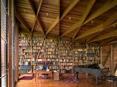 Love this library, the diagonal shelves, the hardwood floor, the piano and the exposed wood beam ceiling... dream house!