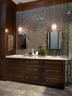 The streamlined vanity conceals a warming drawer and speaks to the man of the house's desire for simplicity. The polished marble countertop and sparkling glass pendant lighting add a feminine touch.