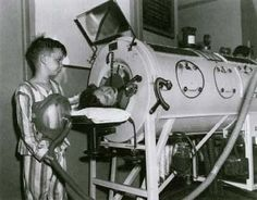 """This photograph, taken in 1949, shows an 8-year-old boy with polio wearing the newly introduced one-pound portable """"Monaghan"""" iron lung arou..."""