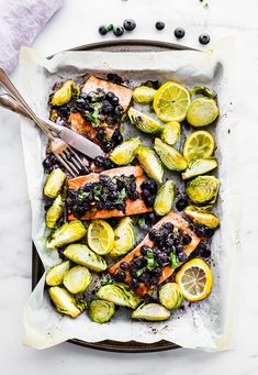 One pan Paleo SUPERFOOD Baked Salmon! This baked salmon recipe is ready in 20 minutes and packed full of nutrients. A nourishing, whole 30 friendly, flavorful meal! Salmon baked with a zippy basil blueberry balsamic topping and crispy Brüssel sprouts!   Get your sheet pan ready for dinner! www.cottercrunch.com