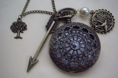 The Hunger Games Inspired Arrow with Mockingjay and Peeta Pearl heart spider web pocket watch locket necklace. $7.80, via Etsy.