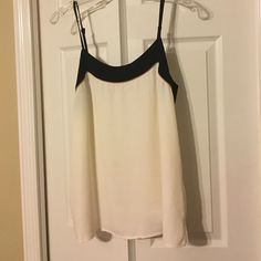 LOFT White Cami - Size L Flowy white Loft cami with black trim around neck line and brown piping. Great under a blazer/ jacket for work or paired with a pair of jeans and heels! There is a faint discoloration on the back of the tank (see pic #4). It's very hard to see, but I want it to be known! LOFT Tops Camisoles