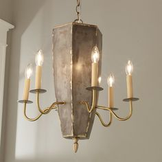 """Check out Rustic Steel Hexagonal Chandelier from Shades of Light This unique chandelier has a hexagonal body in a rustic gray steel finish with brass accents around the seams. Six brass arms hold candelabra sockets with cream colored candle sleeves. An elongated brass finial adds a classic touch to this charming whimsical chandelier. Supplied with 9' of chain, 11' of wire and 5"""" brass canopy. (21""""Hx21""""W). 6x40 watt"""