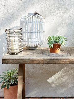 A rustic console topped with two lanterns and a succulent proves the aesthetic power of carefully placed accents.