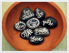 Paint rocks. Corridor creations. provide black rocks in shallow bowl with instruction tag. Also provide larger bowl to place rocks when finished. Put markers in dish painted black with red bow