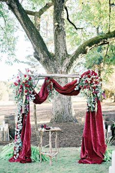 Red Wedding Decorations: Dress up your ceremony altar with a beautiful arch draped in red velvet. It gives a regal look that would perfectly suit a formal red wedding in the winter. | Gorgeous Ideas for a Red Wedding Palette