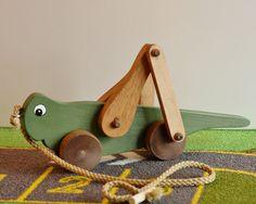 Le corps de la sauterelle est peint avec de la peinture acrylique non toxique à la main. Les jambes et les roues sont colorées. L'artisanat fil tirer le cordon est attaché à un crochet d'oeil qui est collé en place. Comme le jouet est tiré les jambes articulées seront alternativement monter