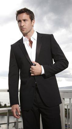 Groot contrast tussen donker pak en overhemd -> zakelijk, afstandelijk. De open boord maakt het toegankelijk.
