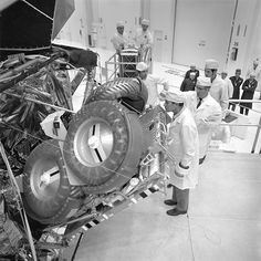 Apollo 16 Commander, John Young, center; and Lunar Module Pilot Charles Duke, foreground, inspect the Lunar Roving Vehicle they will use for transportation on the Moon during a Deployment Test in the Manned Spacecraft Operations Building at the Kennedy Space Center. The Rover is stored in the Ascent Stage of the Lunar Module for the trip to the Lunar surface. This inspection came during a review of Apollo Lunar Surface Experiments at the Spaceport. Launch is set for March 17.