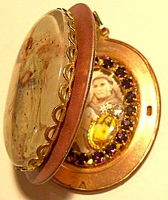 $89 The plum pink enamel front of the shrine pendant has a large oval glass cabochon cameo depicting a Victorian era Angel. Inside: on one side you'll find an image of Saint Anthony holding the Christ child surrounded by dark amethyst rhinestones and a tiny sacred heart of Jesus Christ medal with clear rhinestone accent. The other side is for your personal photo or prayer request.
