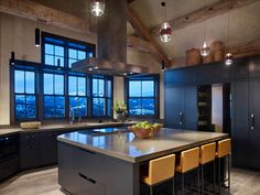 If the windows are on the end over the sink, move the cooktop to the island with modern hood like this.