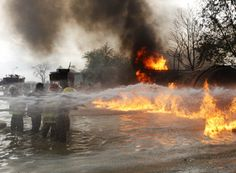 Firefighters spray water on a burning fuel tanker in Kabul April 23, 2012. The cause of the blaze is unknown and police are investigating.