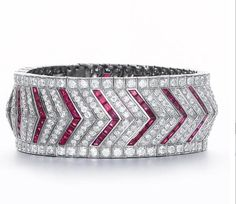 An art deco ruby and diamond bracelet, by Vever, circa 1925 The wide articulated band of old brilliant-cut diamonds alternating with calibré-cut ruby chevrons, all stones in millegrain settings, diamonds approximately 15.00 carats total, unsigned, French assay marks, inner diamter 5.5cm