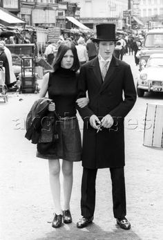 7IT-E2-AA358670 A British girl in miniskirt and a British boy with a top hat walking arm in arm at the Portobello Street Market. London, 1960s Mondadori Portfolio/Mario De Biasi © akg-images / Mondadori Portfolio