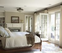 Beautiful traditional bedroom design with tan walls paint color, fireplace, wood bed, French doors, bamboo roman shades, ivory curtains and built-ins.