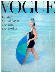 Model Gretchen Harris Photo Richard Rutledge Model standing in ocean with open green and blue umbrella, wearing knitted black maiilot of DuPont and water-velvet cap by Adolfo of Emme, and Greta Pal…