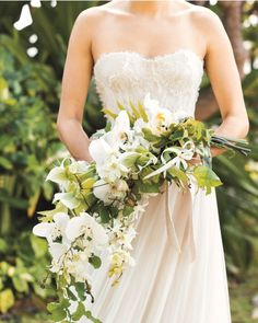 "This loose, cascading bouquet lets you carry the lush, natural beauty of the archipelago down the aisle. Plus, none of its buds—from the array of crisp white phalaenopsis, lady's slipper, dendrobium, and cattleya orchids to the green passion vine—will wilt in warm temperatures. The Details: Samuelle Couture ""Cecelia"" gown, $10,000; samuellecouture.com."