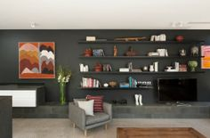 Exterior:Black Wall Design With Open Bookcase With Modern TV Sets With Short Stone Table And Grey Stylish Arm Chair The Toorak House Designs...