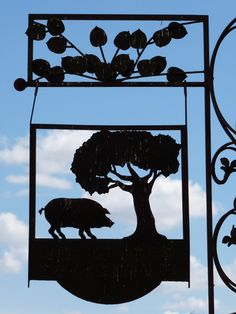 This sign hangs outside La Almazara, a shop selling artisanal food products such as jamon iberico, just up from the Plaza Major in Trujillo, Extremadura, Spain.  It shows a pig foraging under an oak tree, which is the source of Extremadura's famous 'bellota' (acorn) ham from acorn-fed Pata Negra pigs.