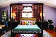"""After: Bedroom: Thom's solution: """"Hang ikat, or flame-stitched, curtains near the ceiling and extend them horizontally past the window to create a dramatic backdrop for the bed."""""""