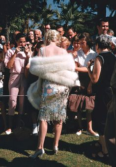 Marilyn Monroe photographed by Richard Miller signing autographs for fans on the set of Some Like It Hot