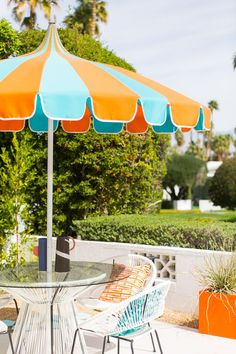 Striped blue and orange umbrella on a mid-century modern Palm Springs patio surrounded by desert plants and decor.